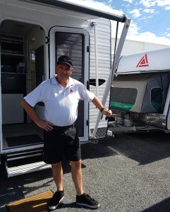 New Age Caravan Sales Team member holding awning